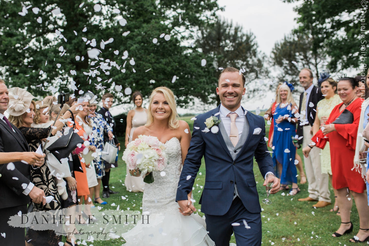 confetti wedding photo at blake hall with groom laughing