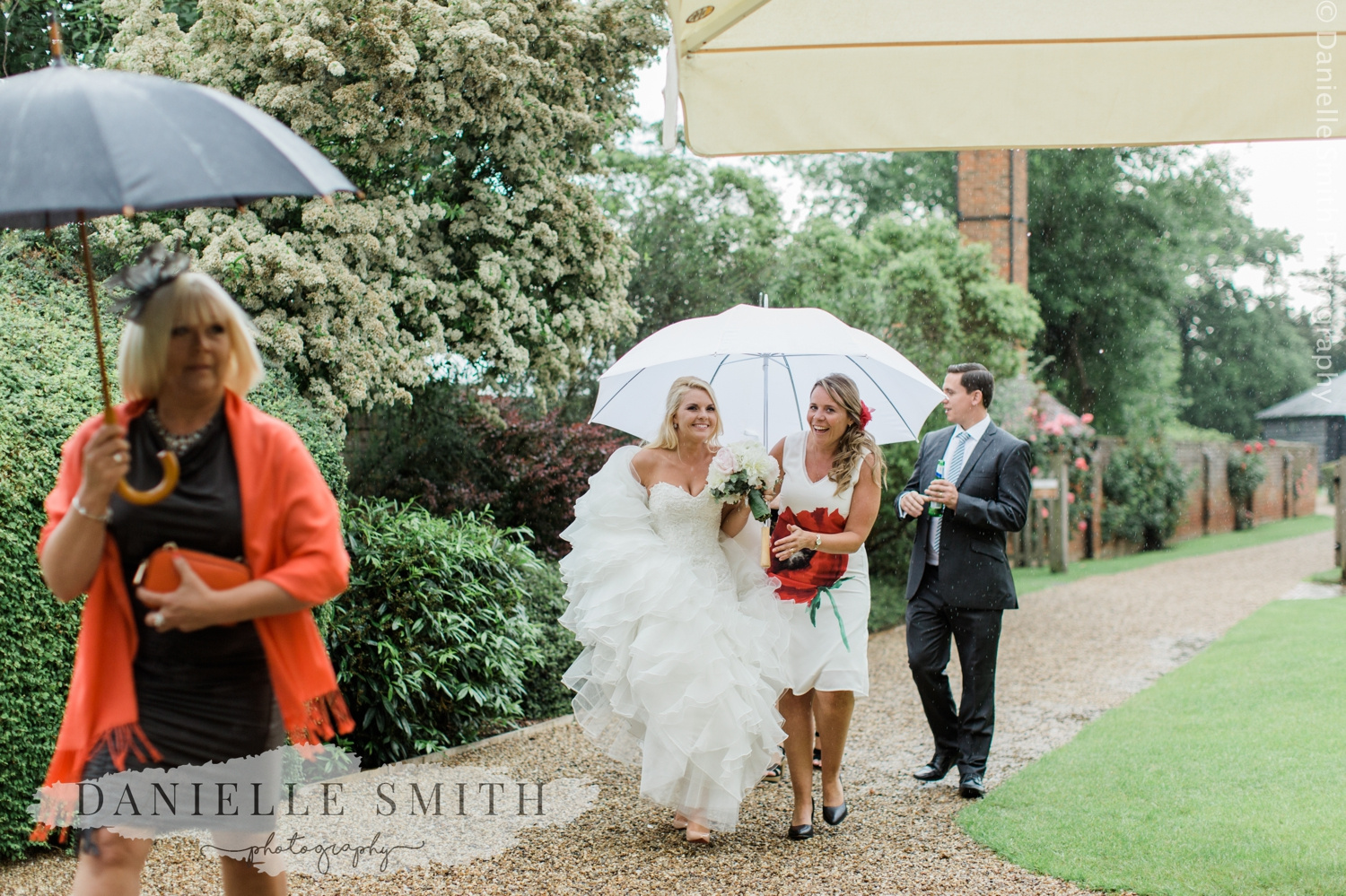 bride walking in rain with umbrella