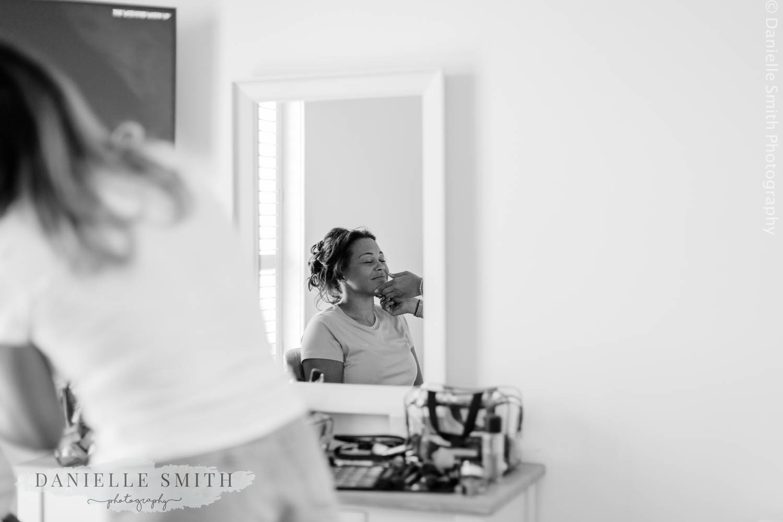 bride having make up done in mirror