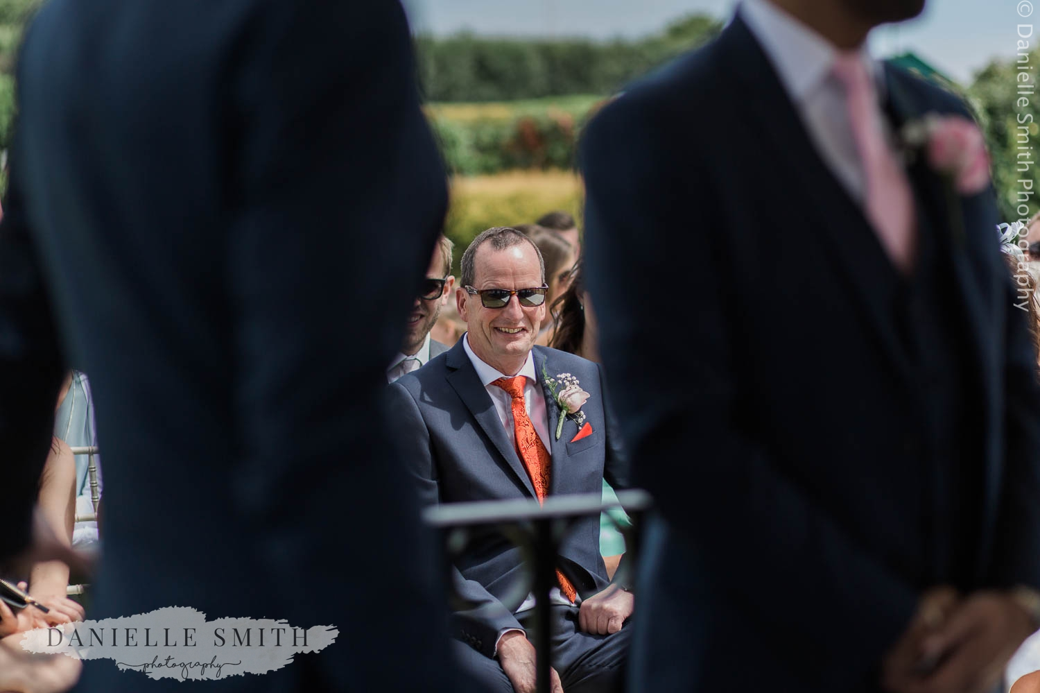 father of groom sitting at outdoor ceremony
