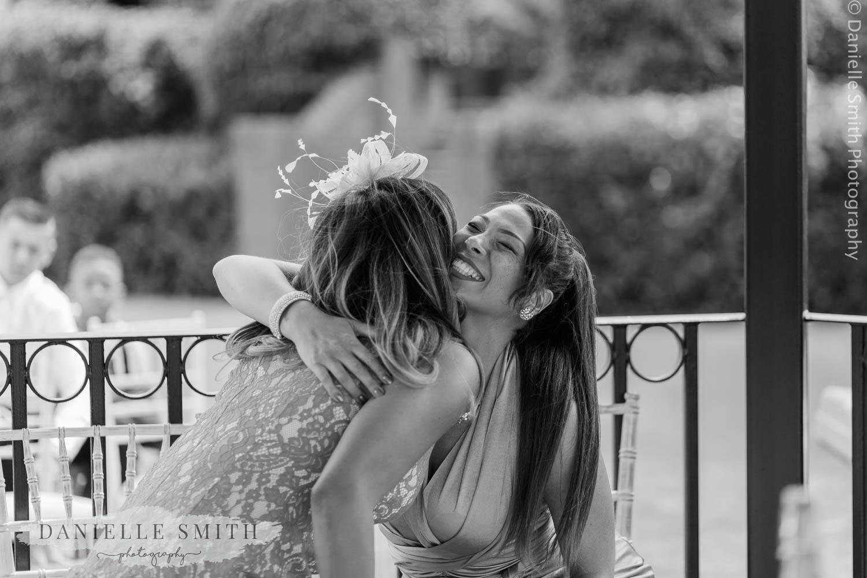 ladies hugging at outdoor wedding ceremony