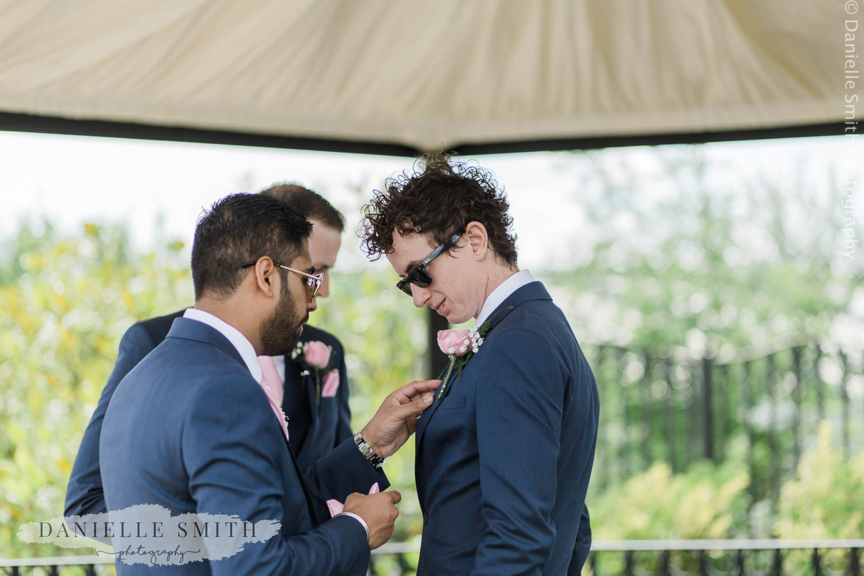 groom and groomsmen helping eachother
