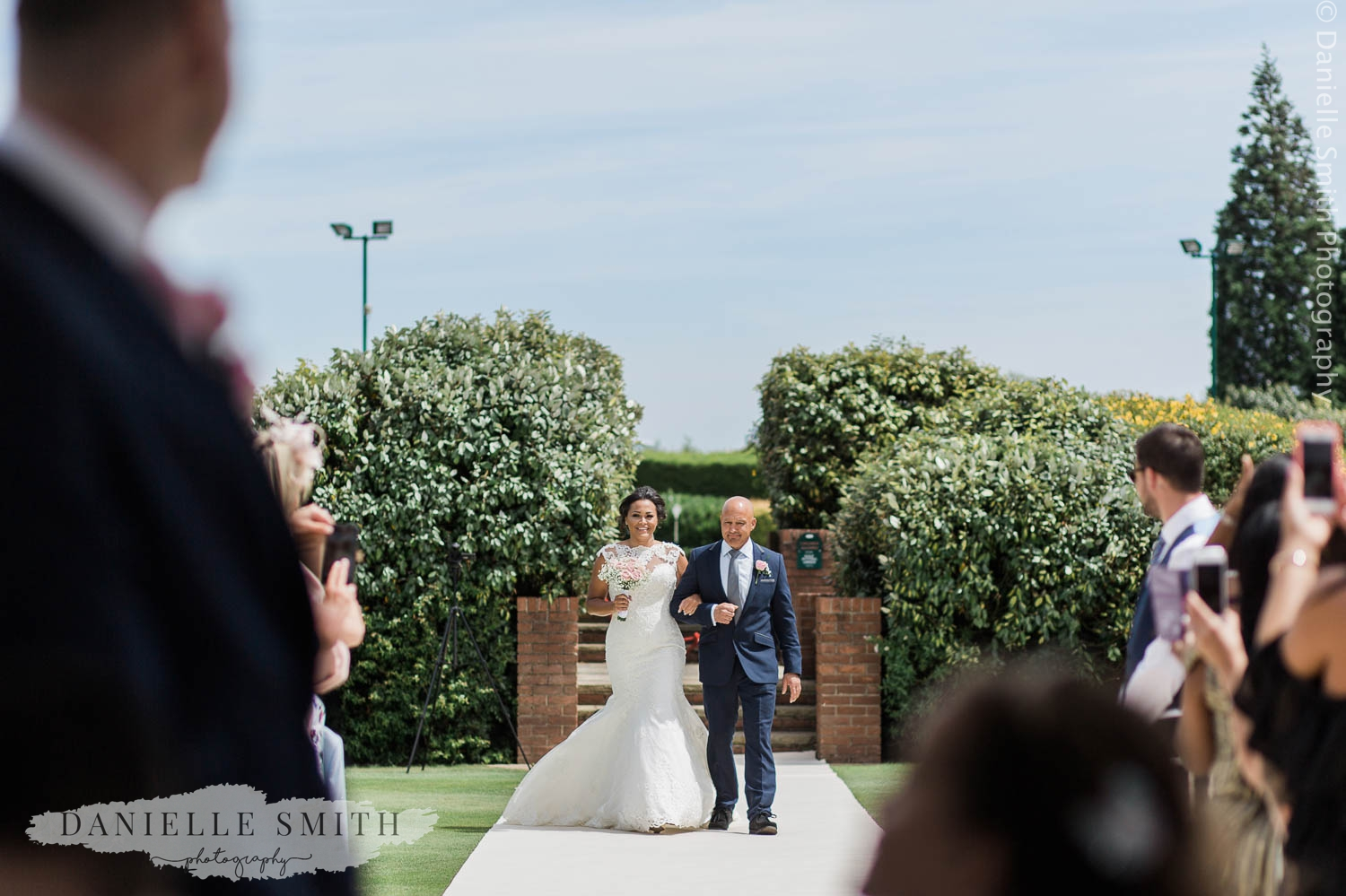 father walking daughter down aisle outside