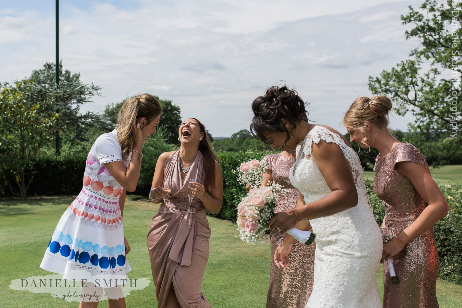bride and bridesmaids laughing in gardens