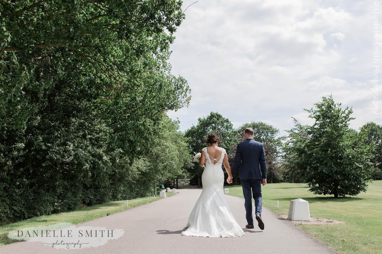 bride and groom walking down drive