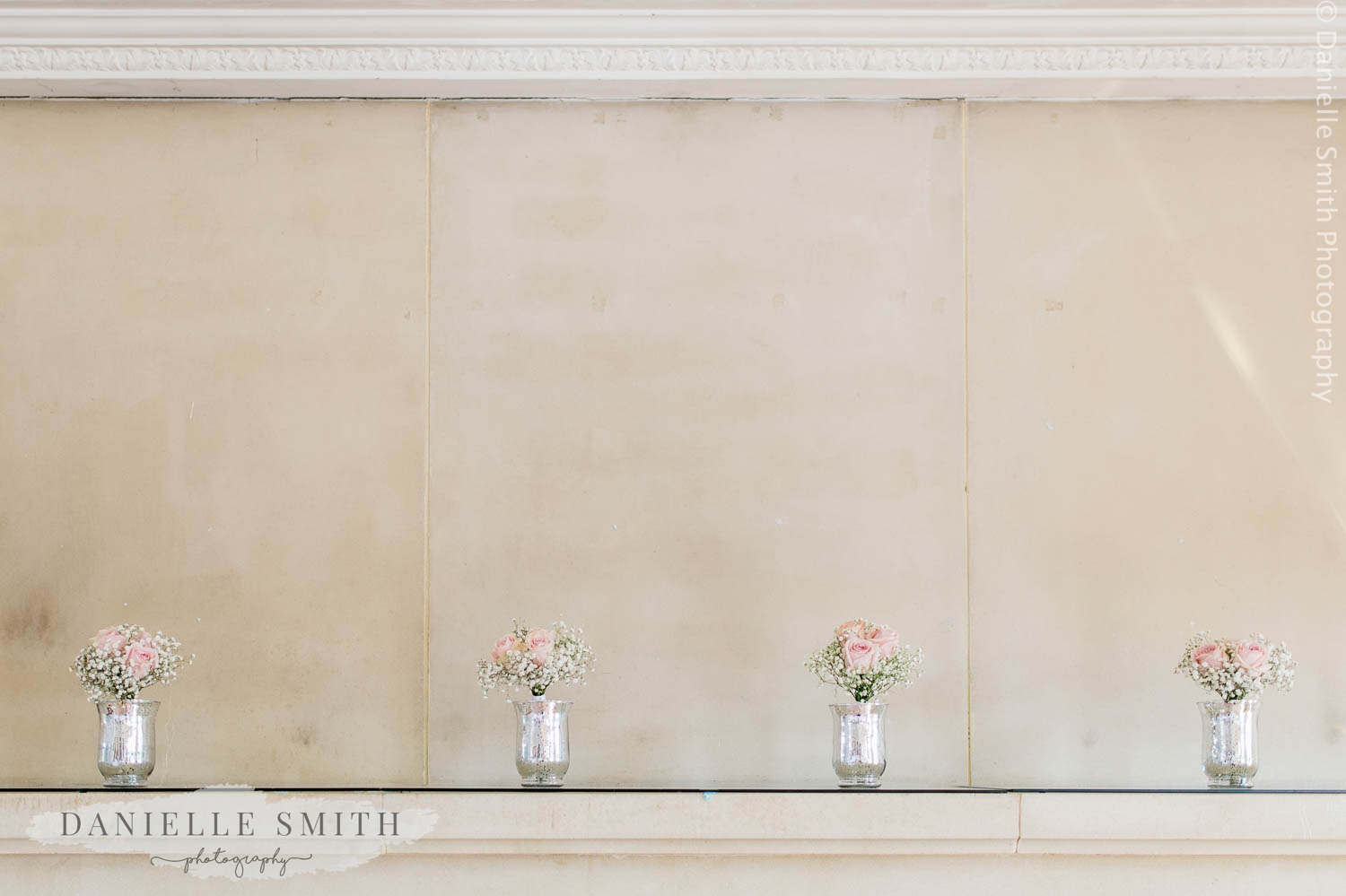 small jars of flowers on fire place at wedding