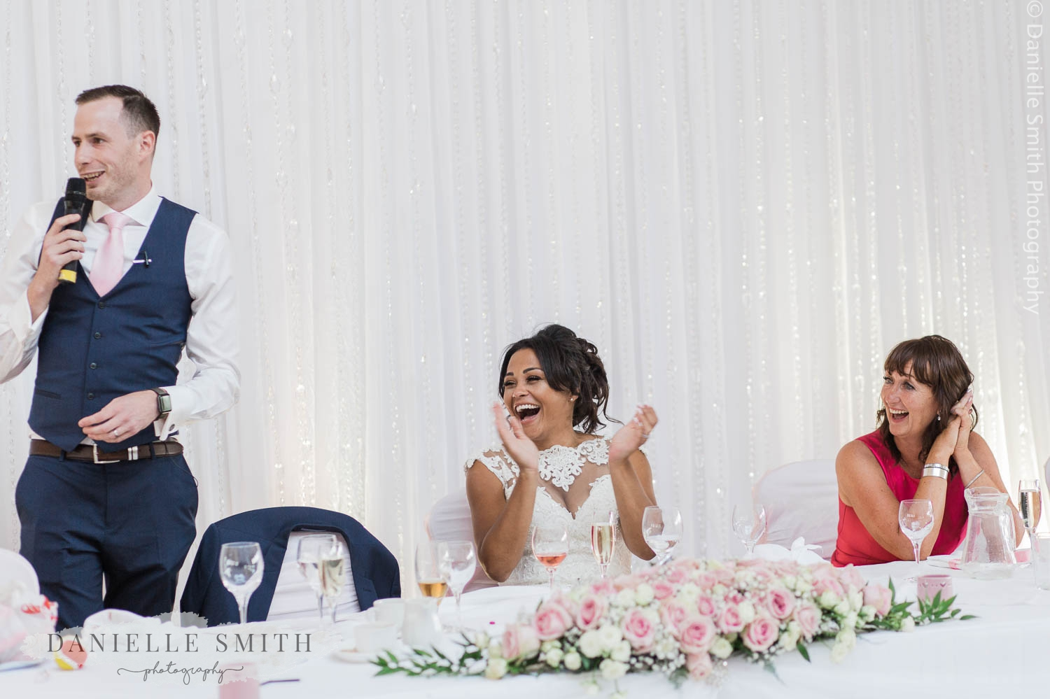 bride clapping at top table