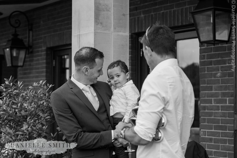 groom holding son at wedding