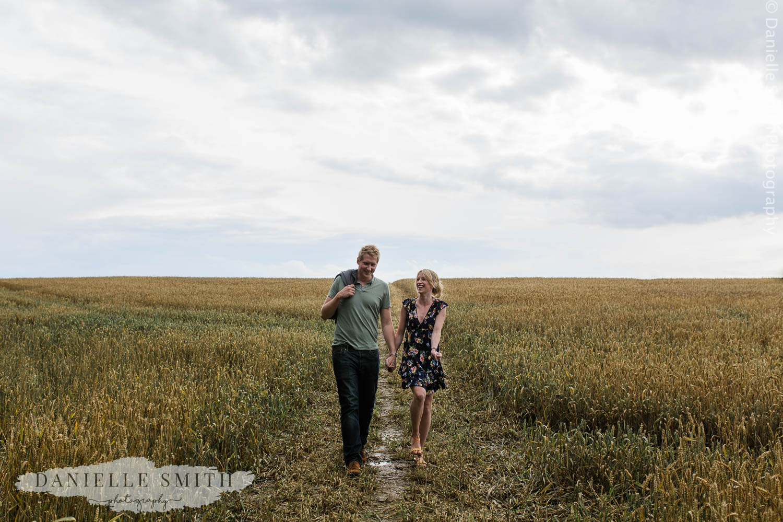 couple walking through corn field