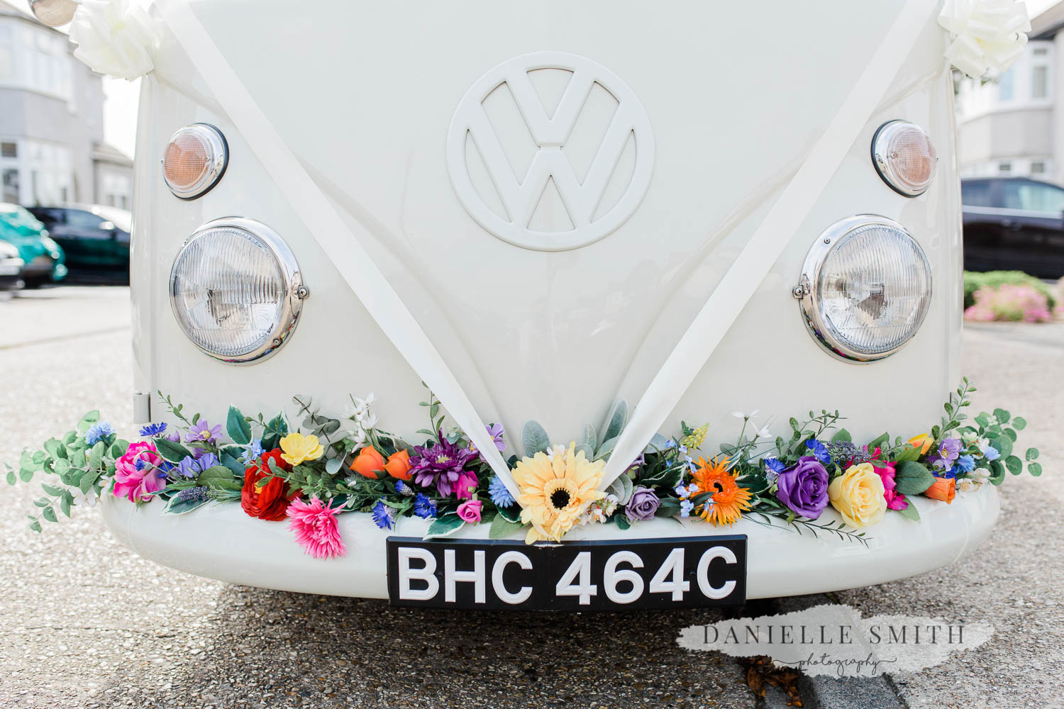 white VW camper van with colourful flowers