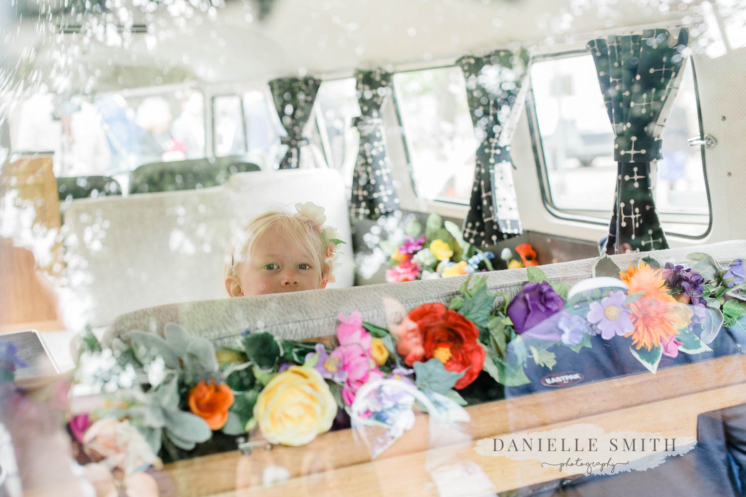 little girl in back of camper van with colourful flowers