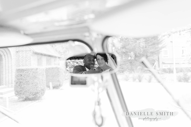 bride and groom having selfie in car mirror
