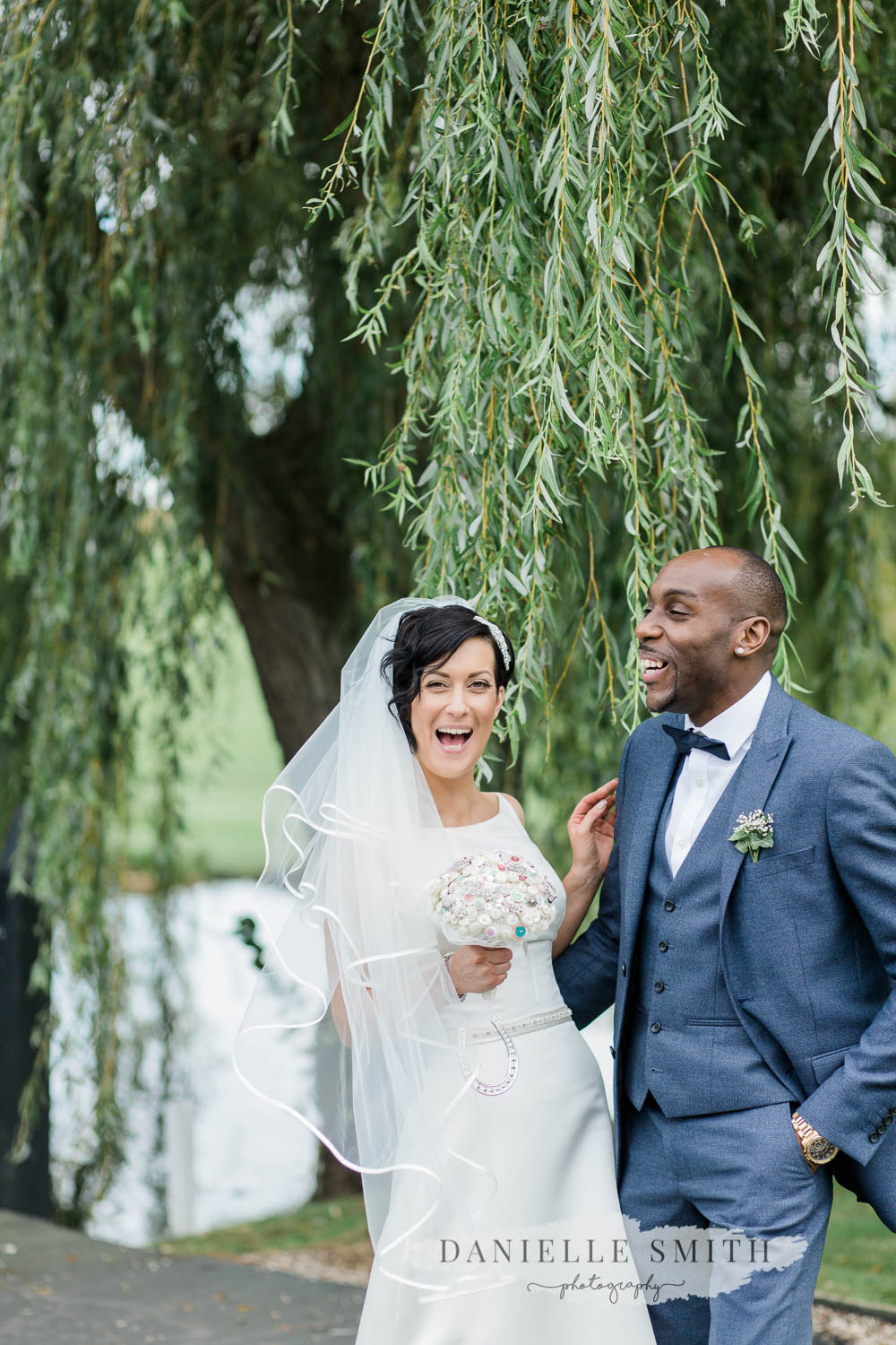 bride and groom laughing in front of willow tree