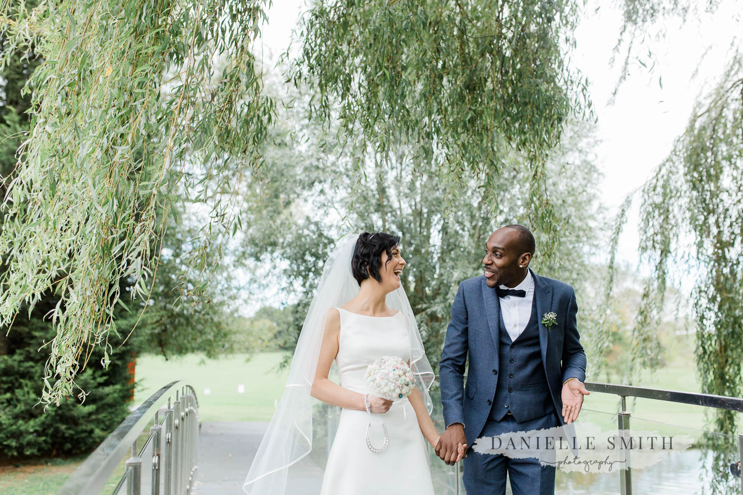 bride and groom walking with willow tree behind