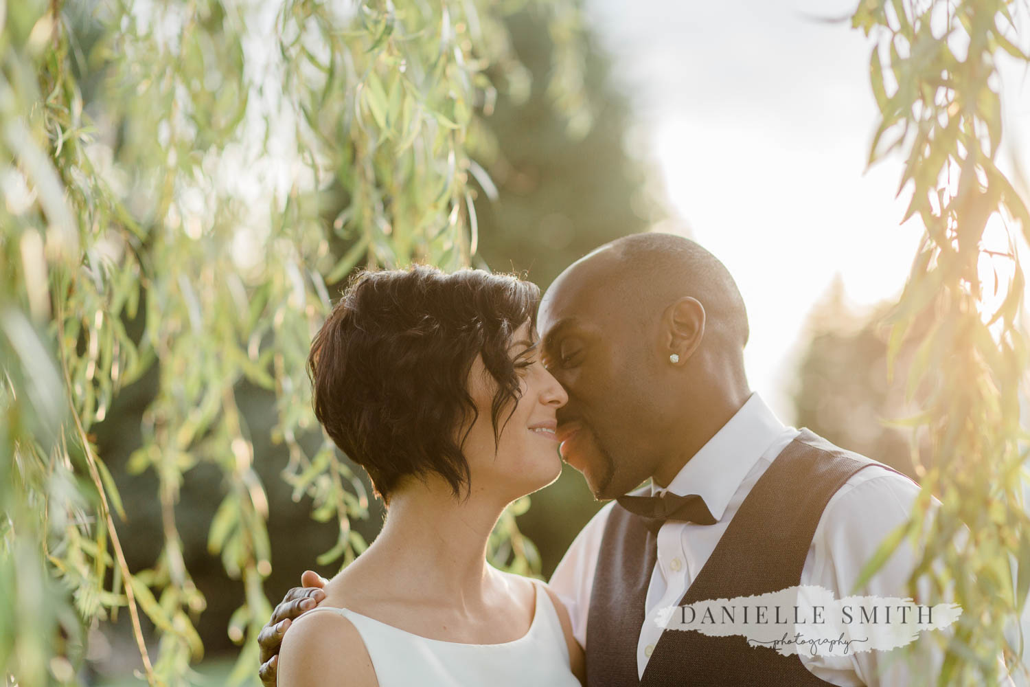 intimate photo of bride and groom at sunset by willow tree
