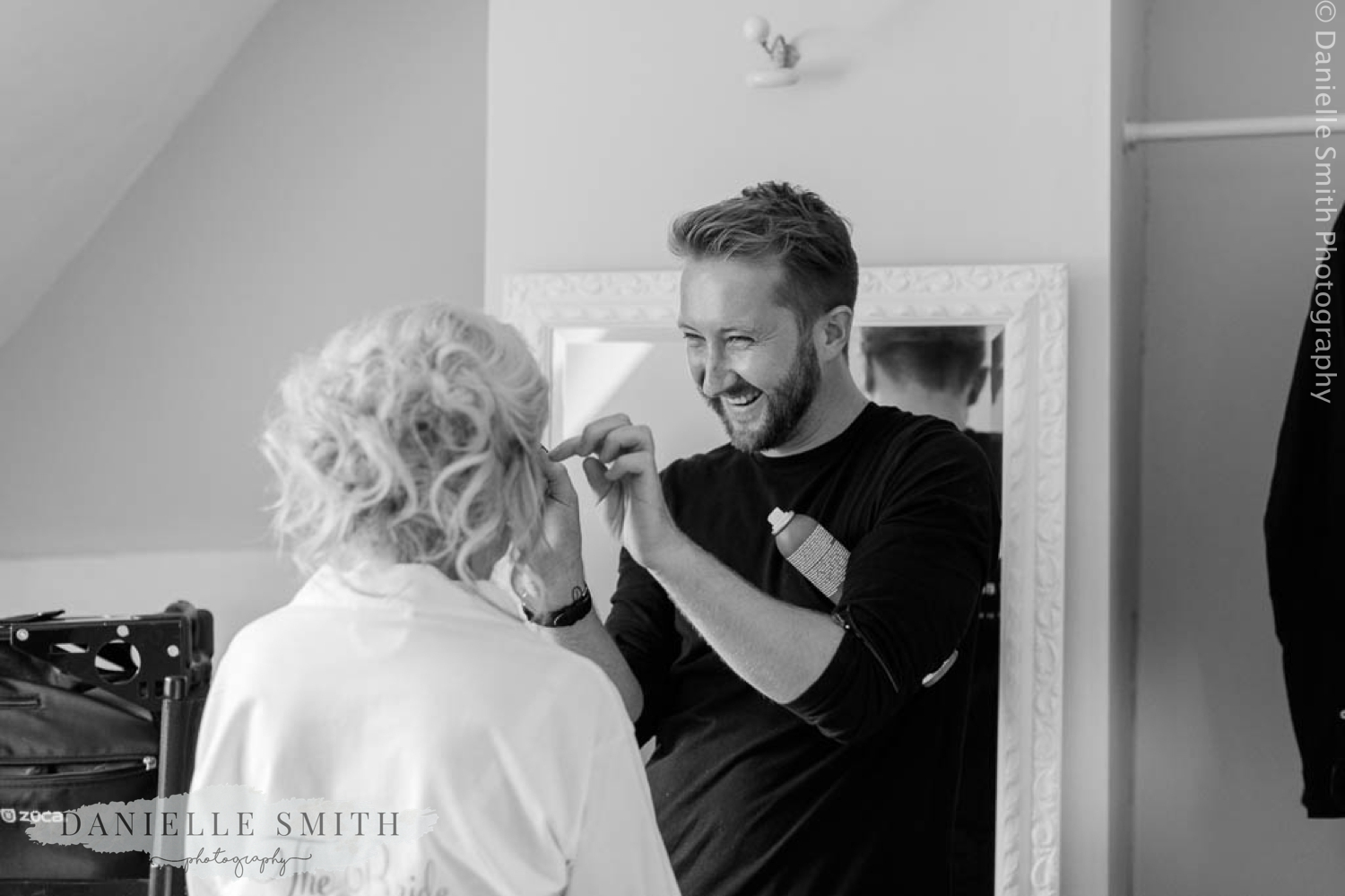 hair dresser laughing while doing brides hair