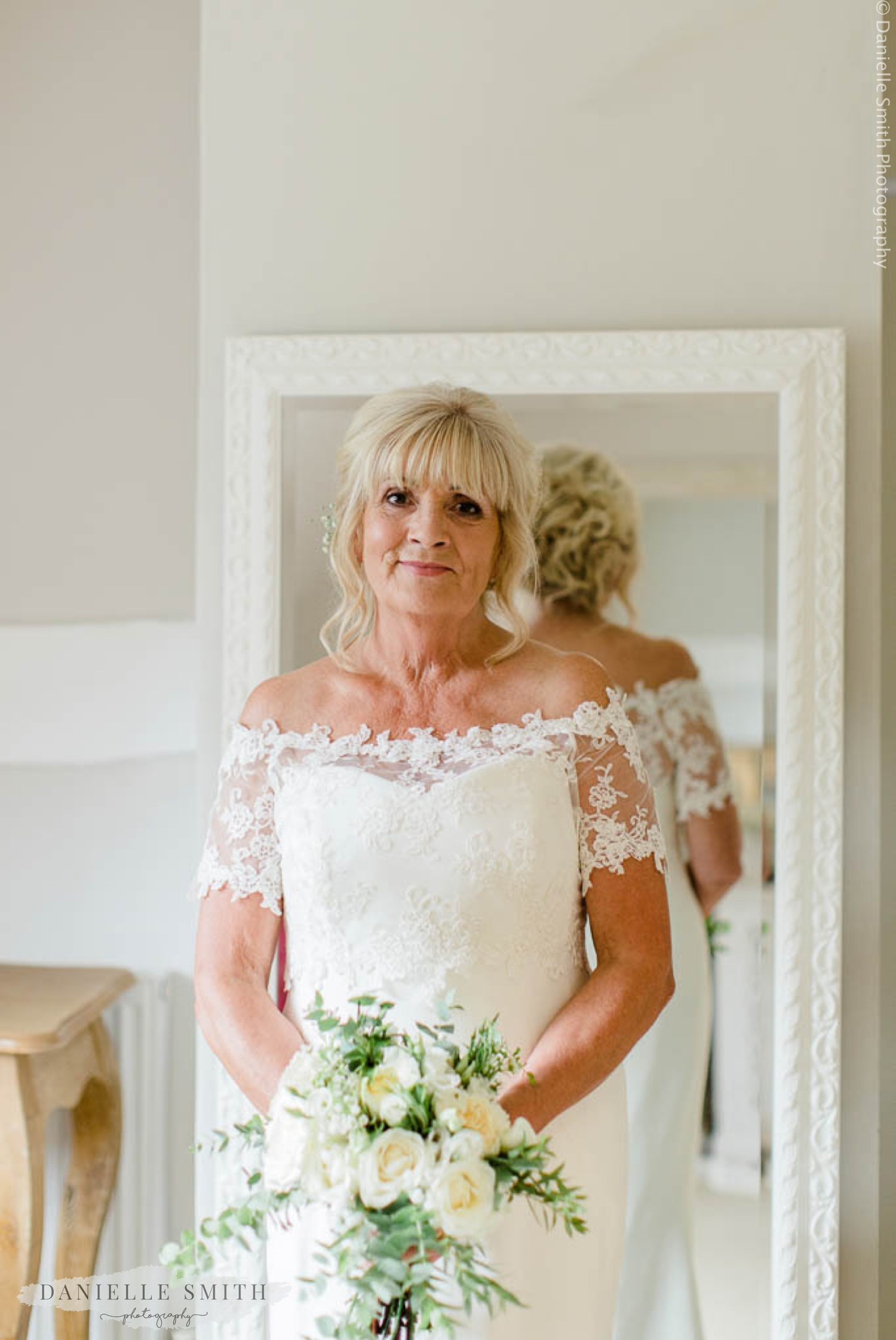 older bride holding ivory bouquet