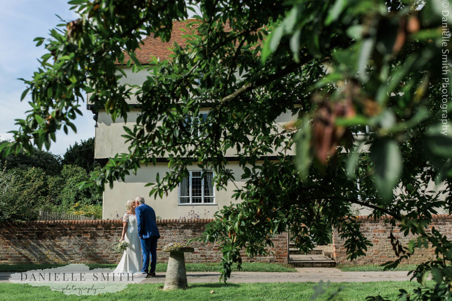 bride and groom kissing outside houchins farm house