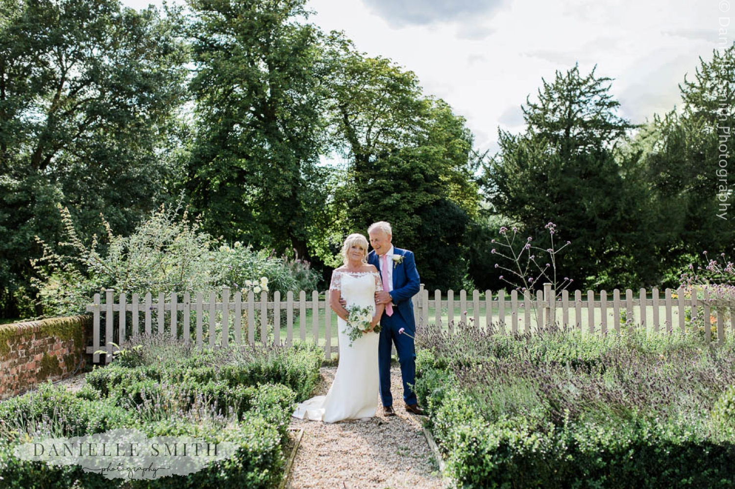 bride and groom in gardens outside farmhouse