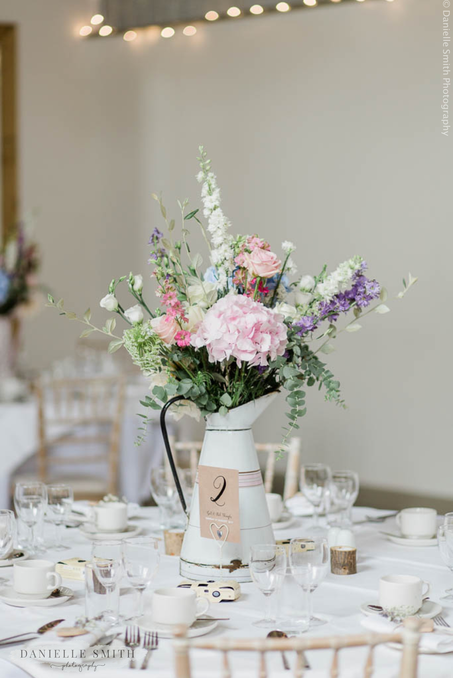pastel flowers in jug on wedding table