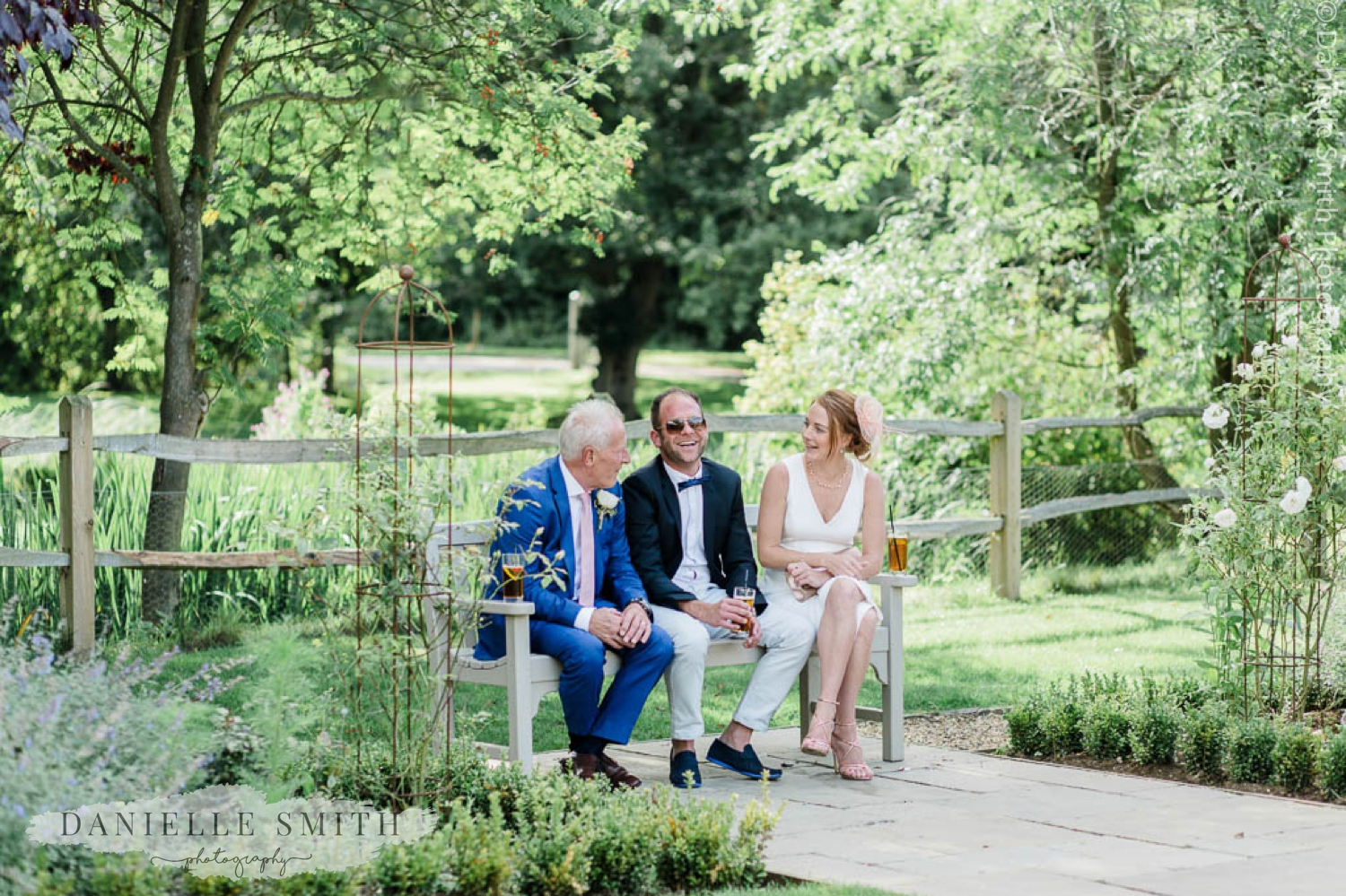 groom and 2 guests sitting on bench in gardens - houchins wedding photography