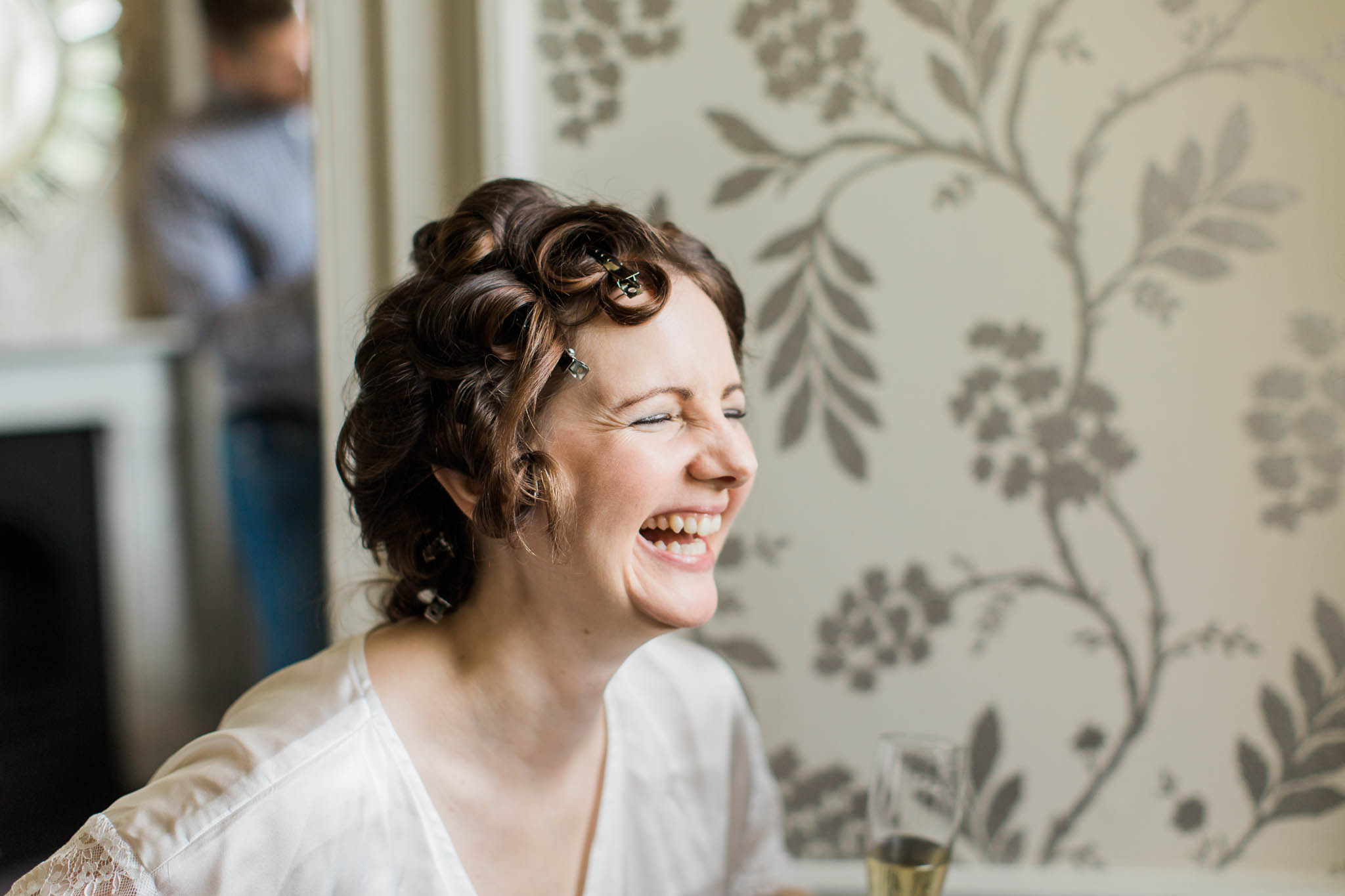 bride laughing with hair in curlers - morden hall wedding