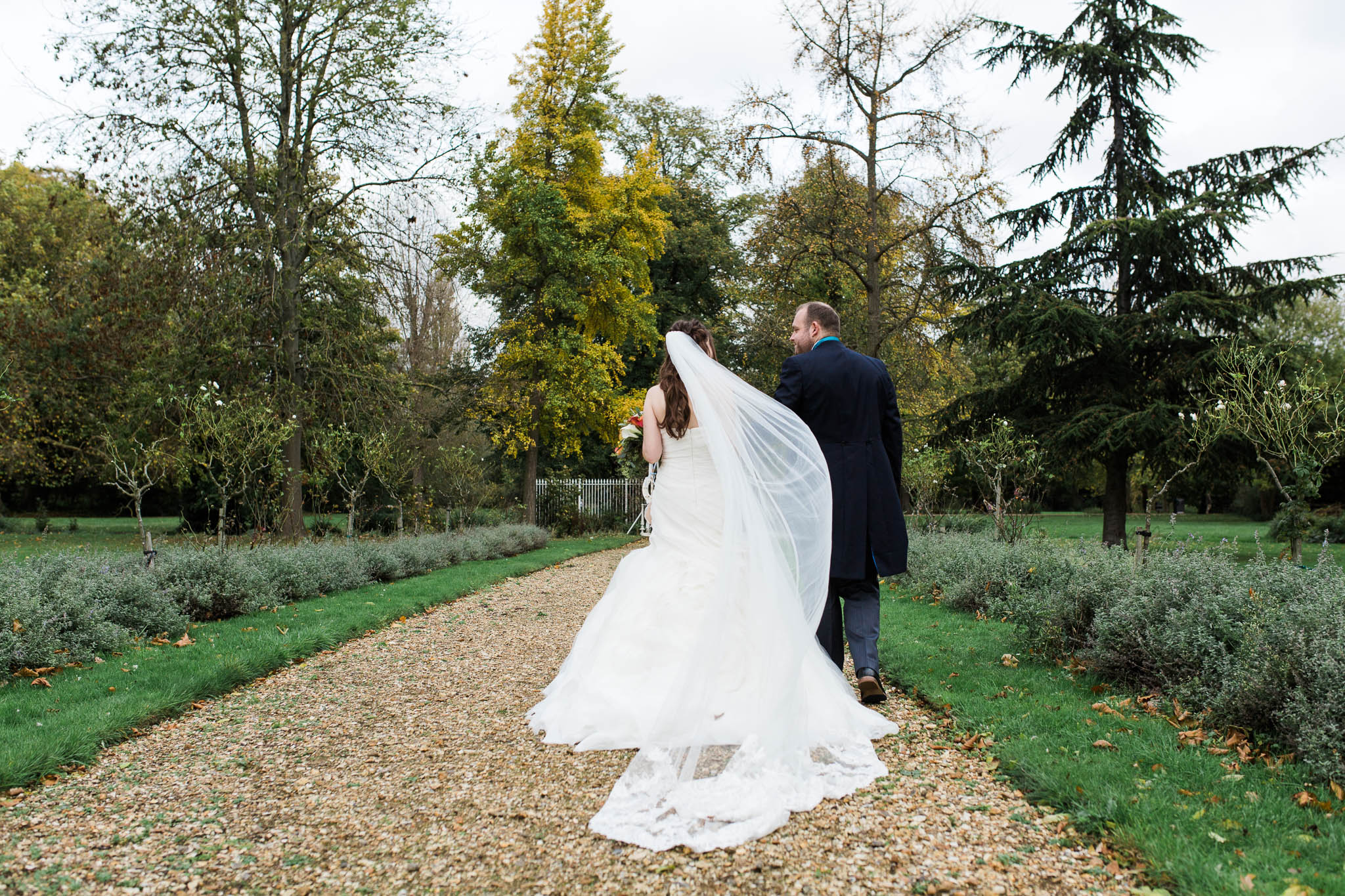 bride and groom walking away and veil blowing in wind - autumn wedding