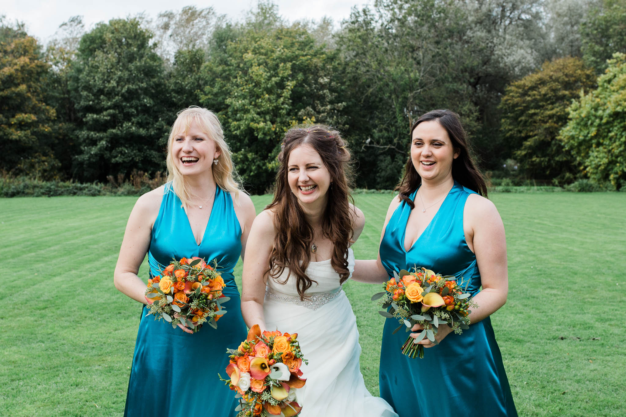 bride laughing with bridesmaids at autumn wedding