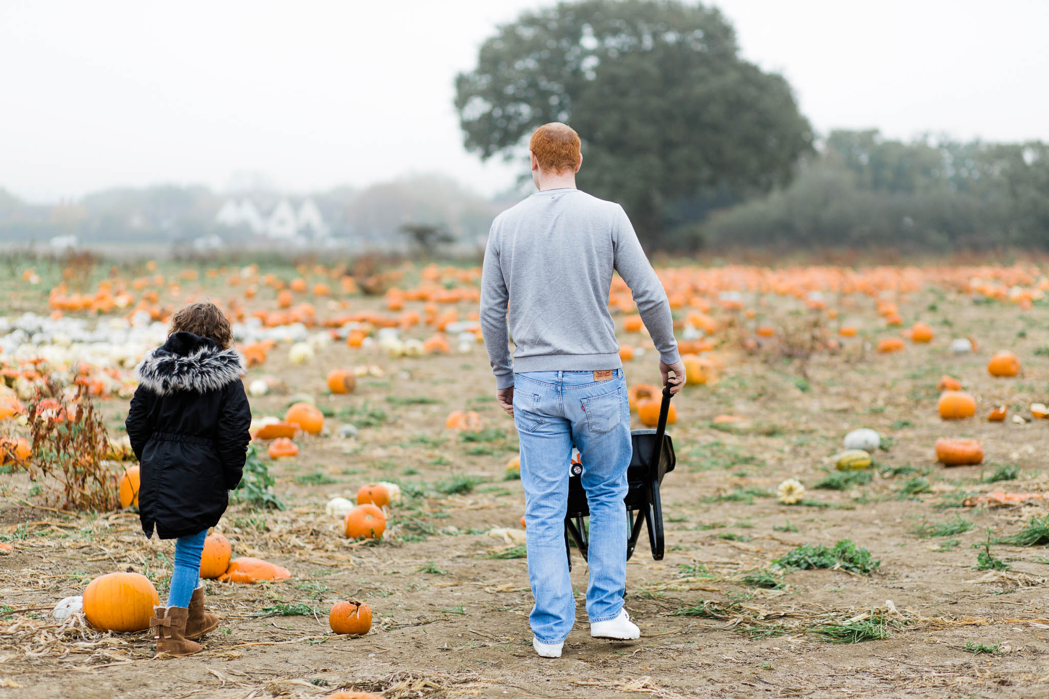 father and daughter walking through pumpkin patch