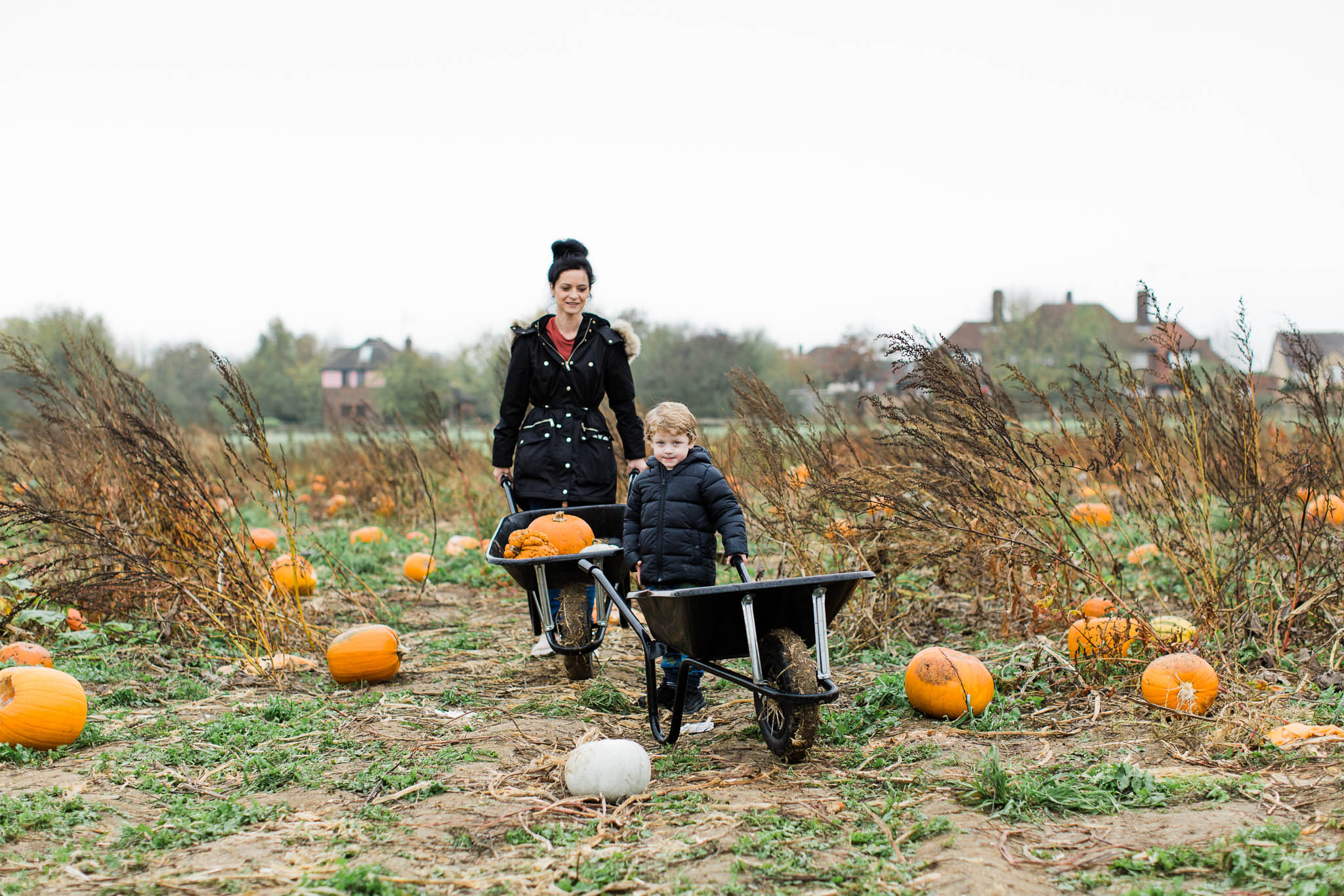 mother and son pumpkin picking