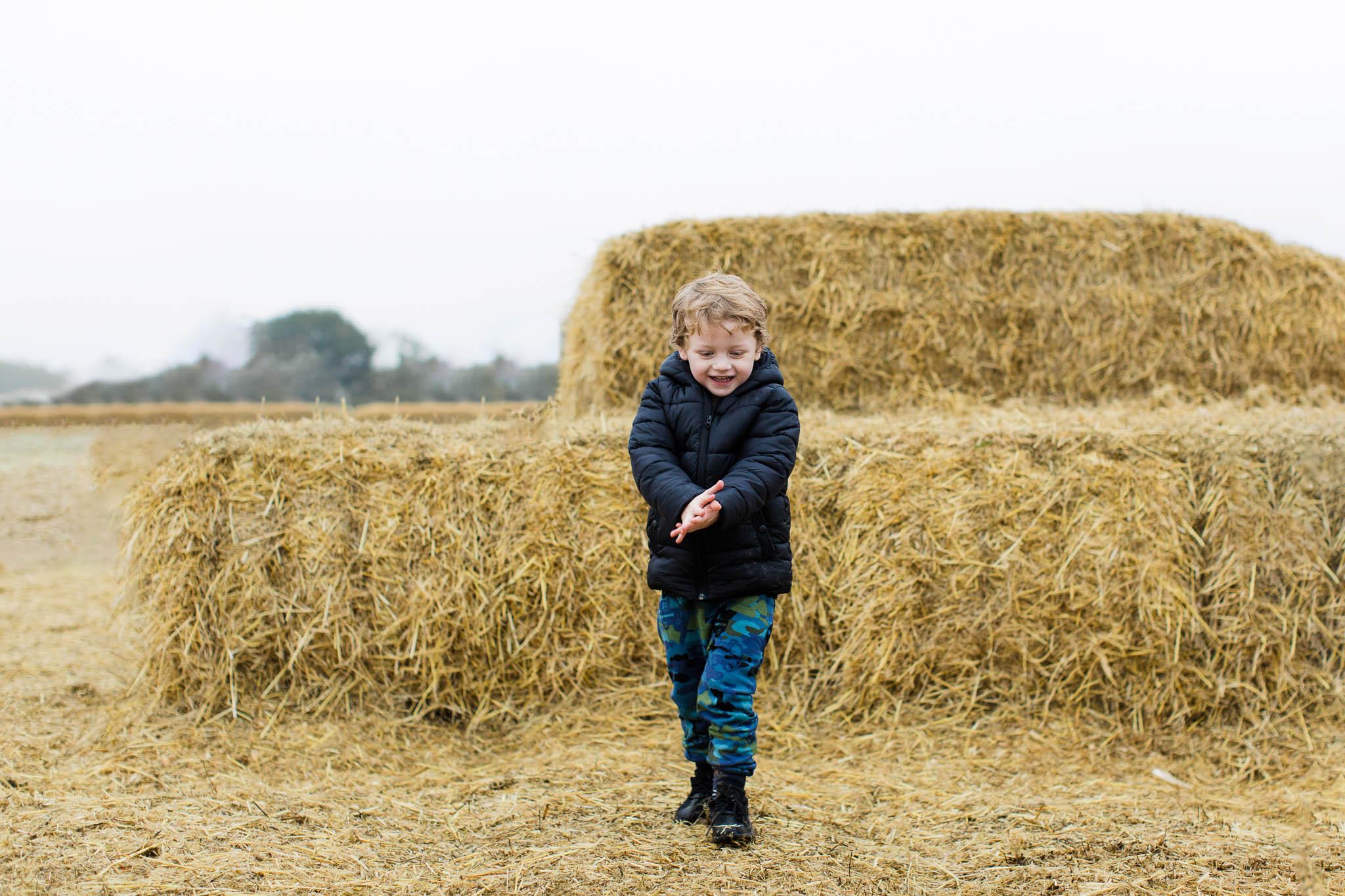 boy smiling next to hay stacks
