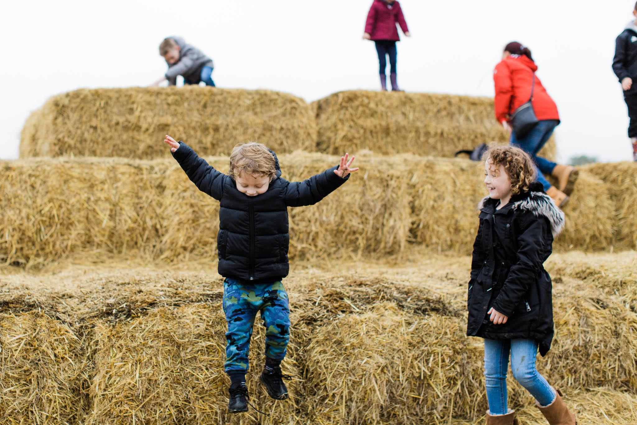 boy jumping off hay stacks