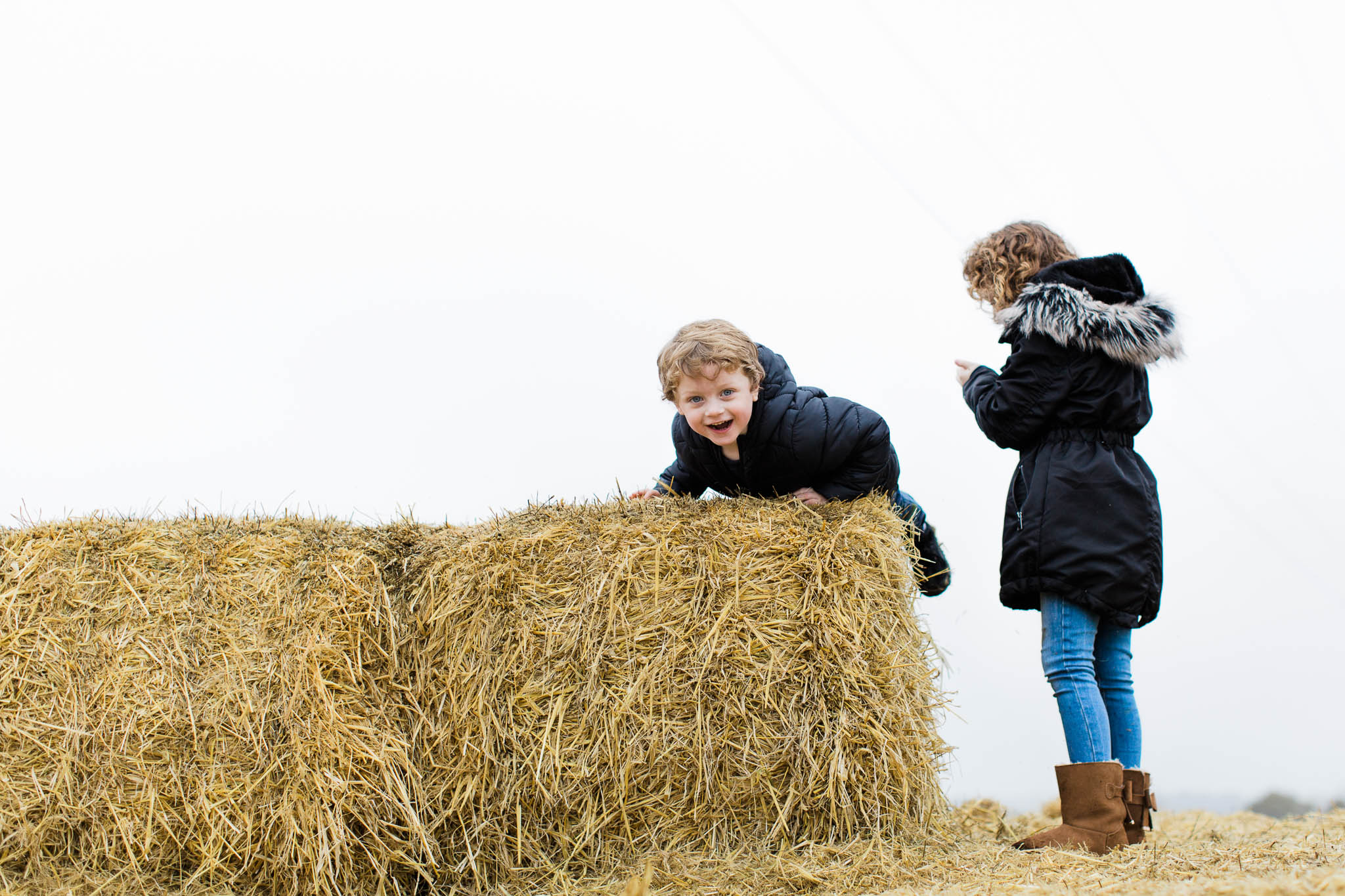 brother and sister climbing on hay stacks