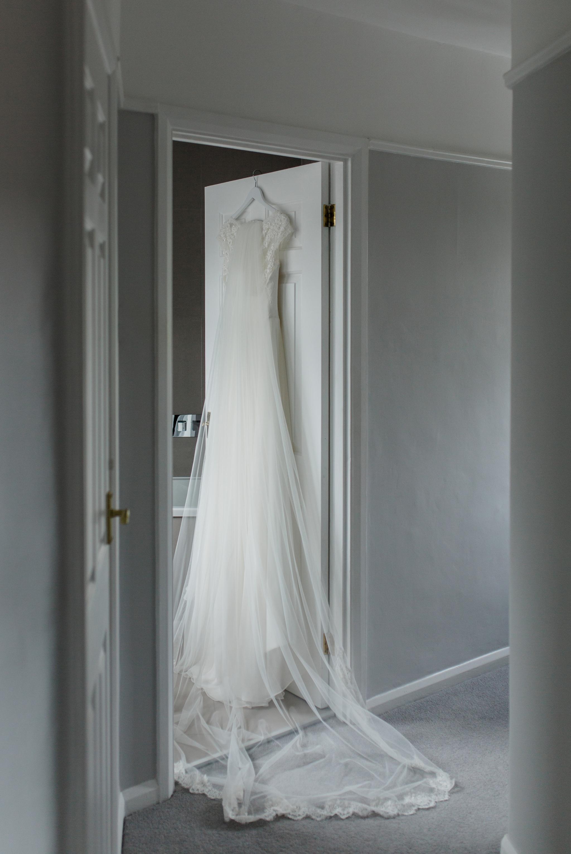 charlotte balbier wedding dress hanging on door