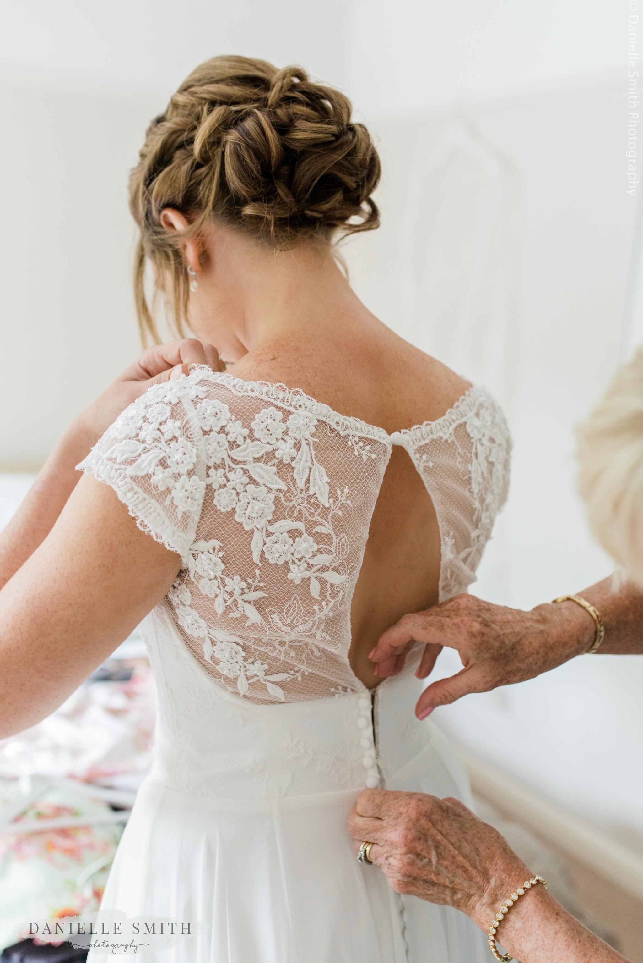 mum doing up back of brides dress