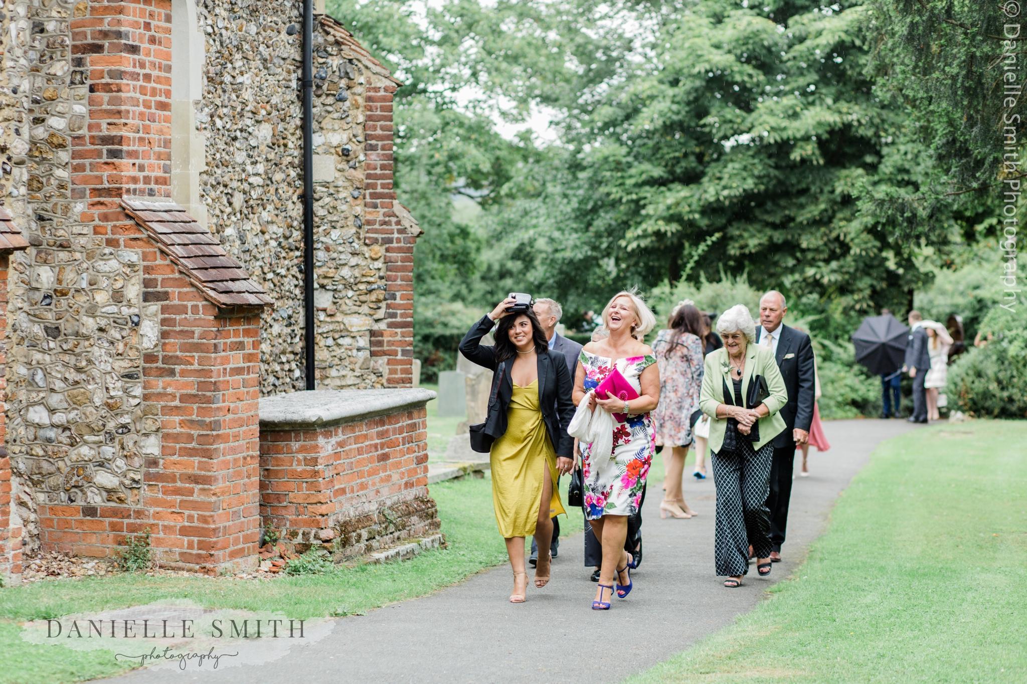 wedding guests walking to church as it starts raining