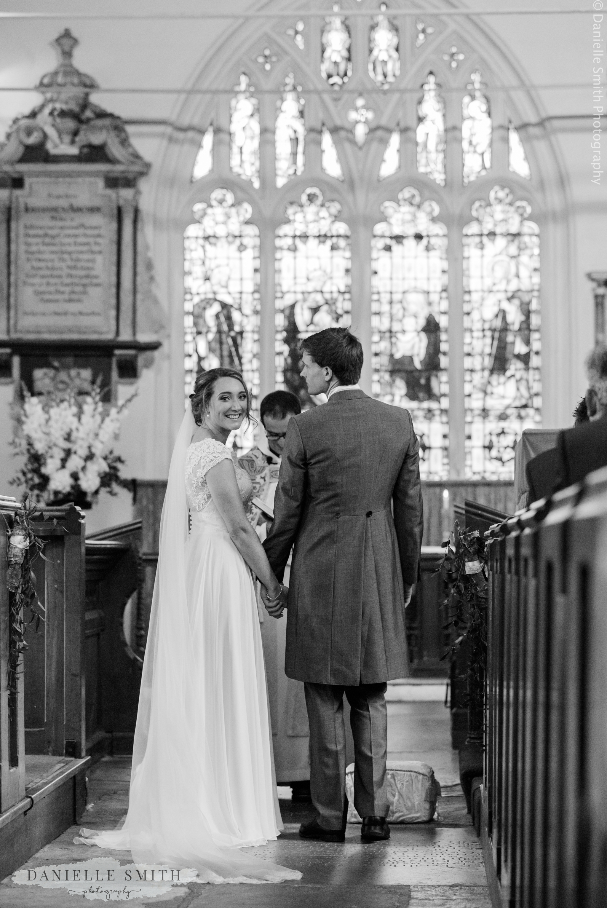 bride looking back at guests in church