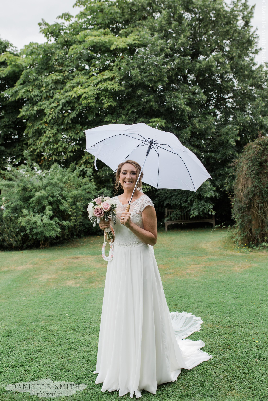 bride standing under umbrella