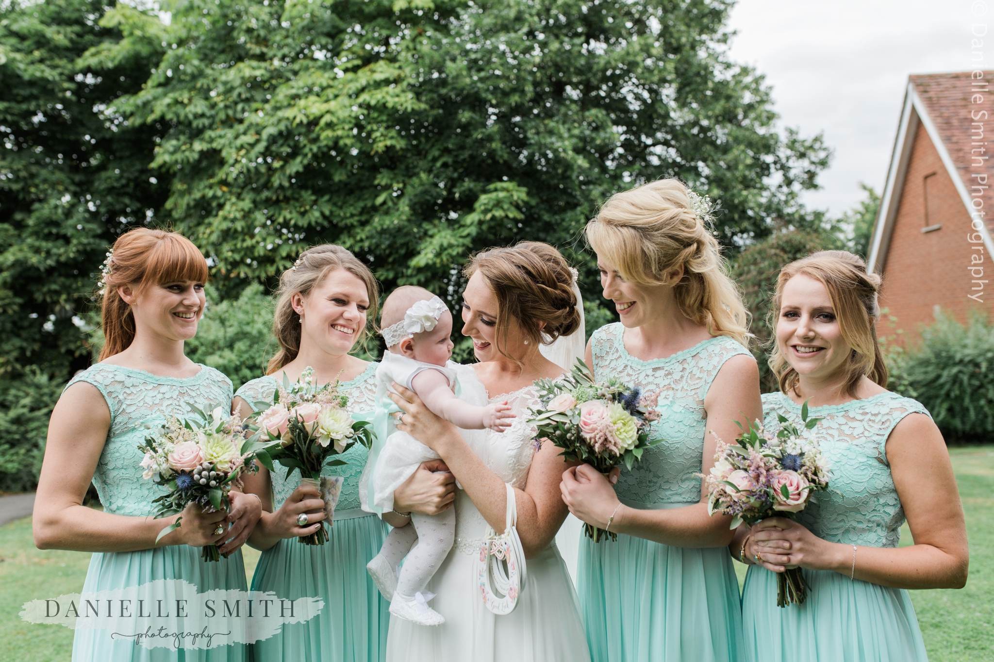 bride holding baby flower girl with bridesmaids