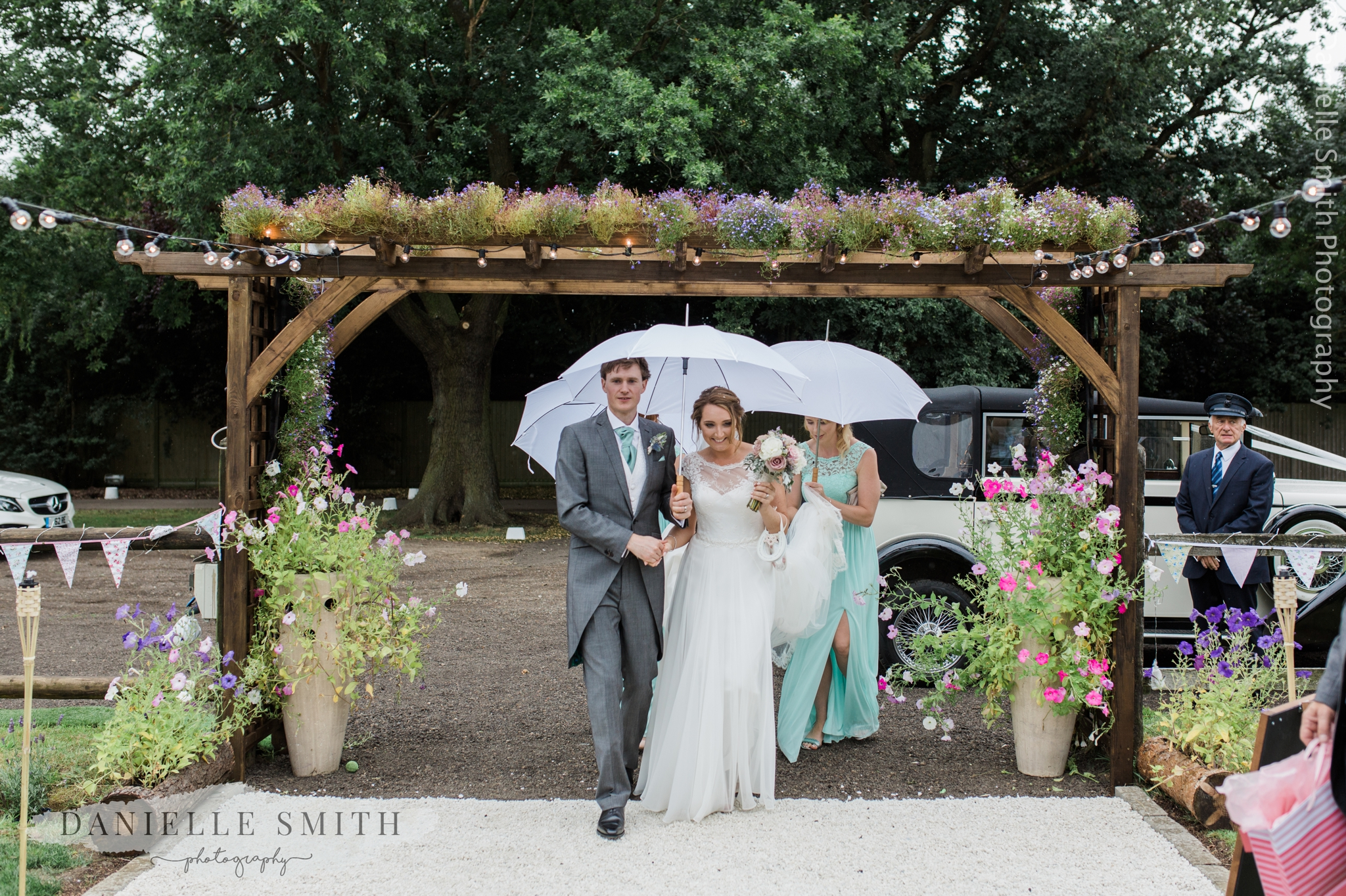 bride and groom arriving in rain with umbrellas - relaxed marquee wedding