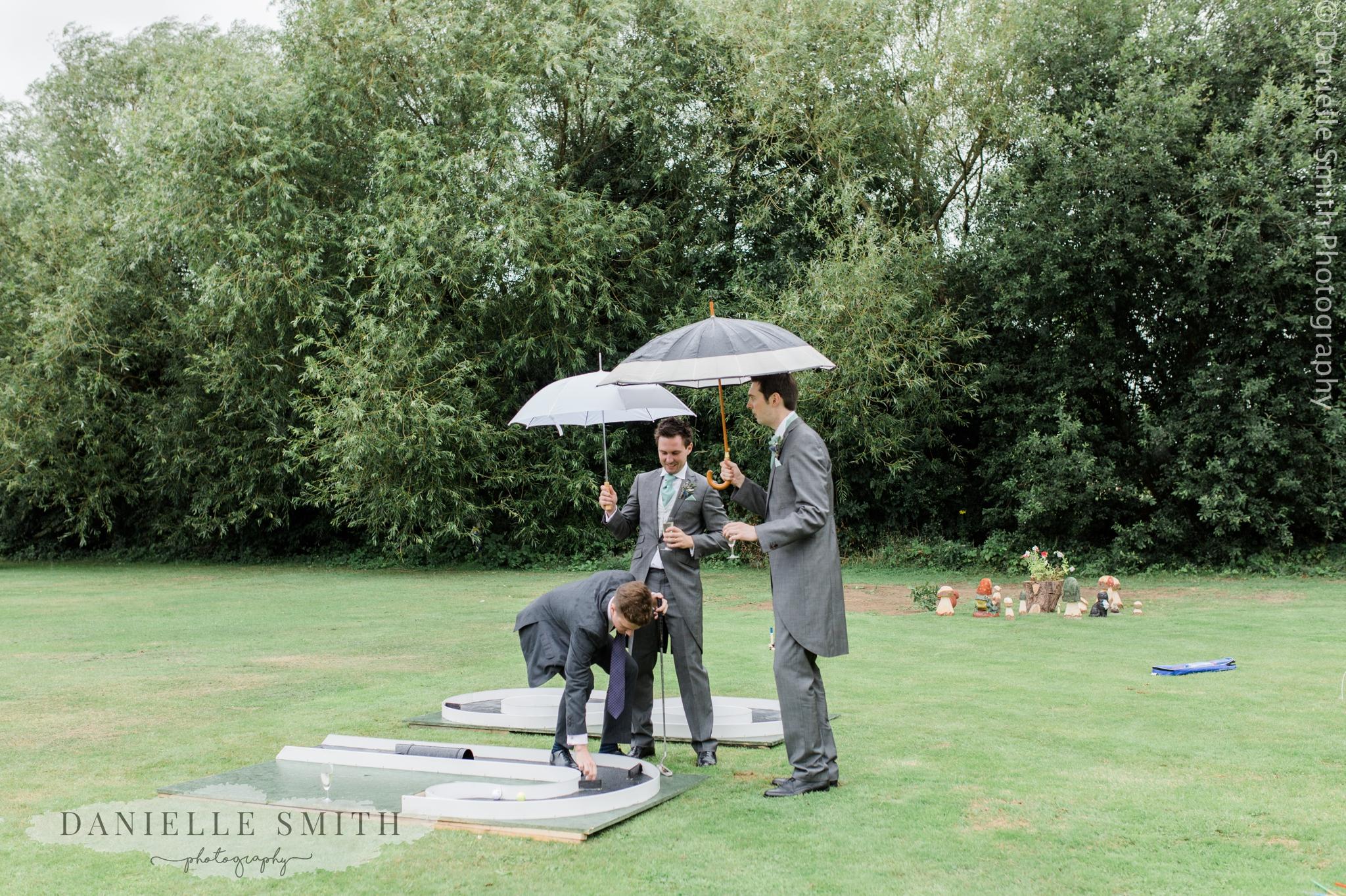 groomsmen playing mini golf in rain