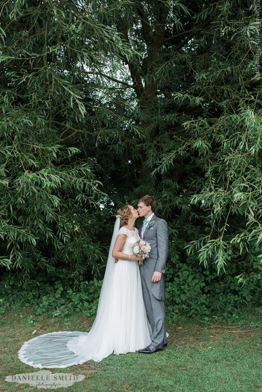 bride and groom kiss under tree