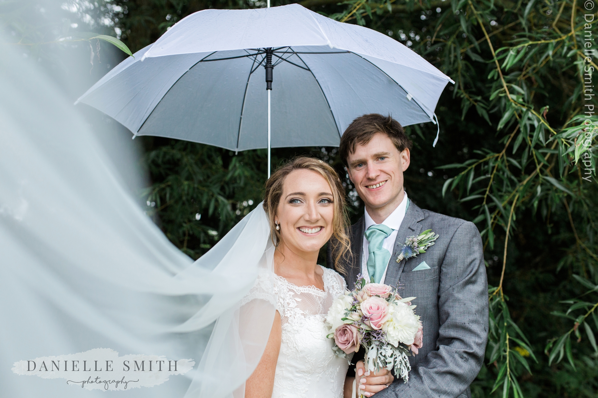 bride and groom with umbrella and veil