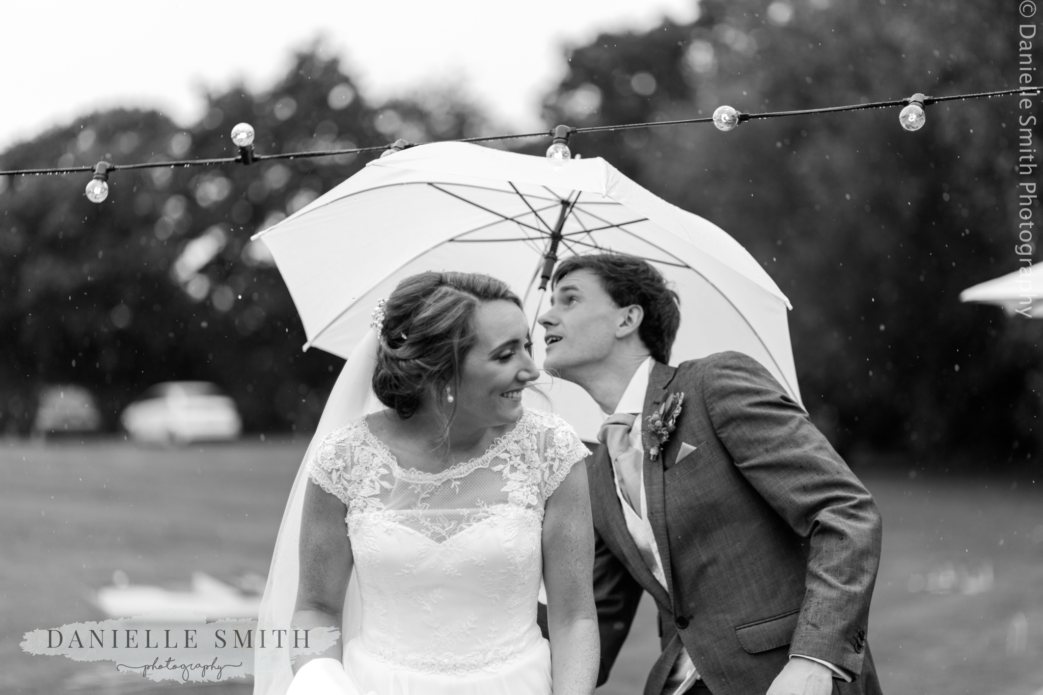 bride and groom ducking under lights with umbrella