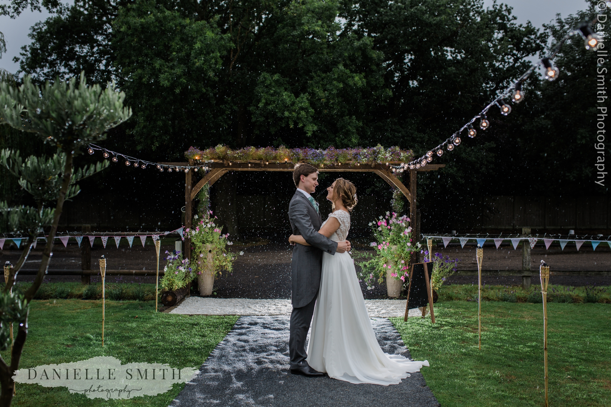 bride and groom standing in rain - relaxed marquee wedding