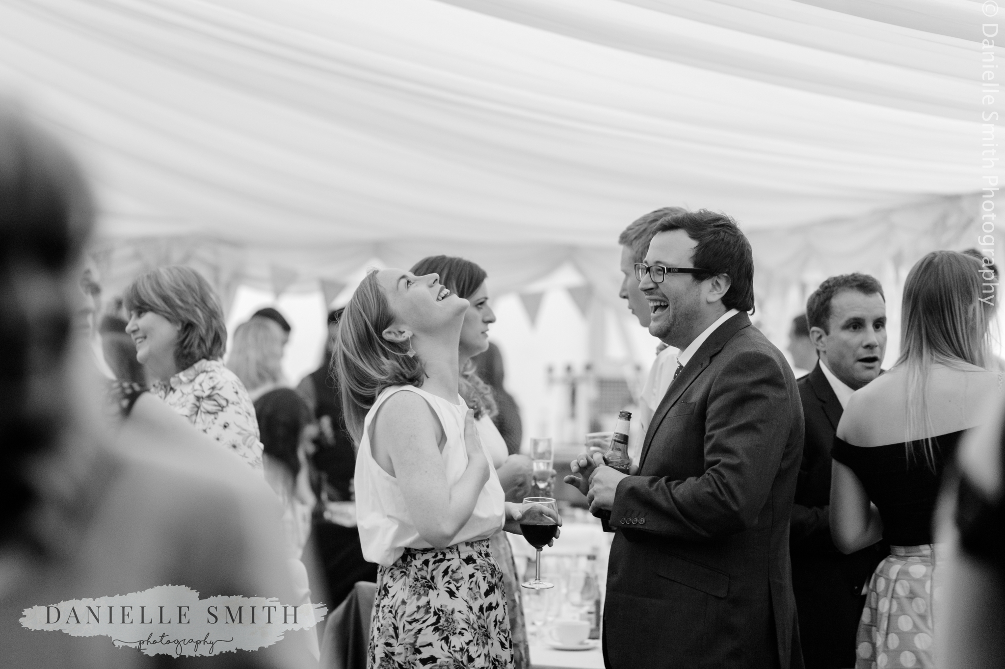 wedding guests laughing - relaxed marquee wedding