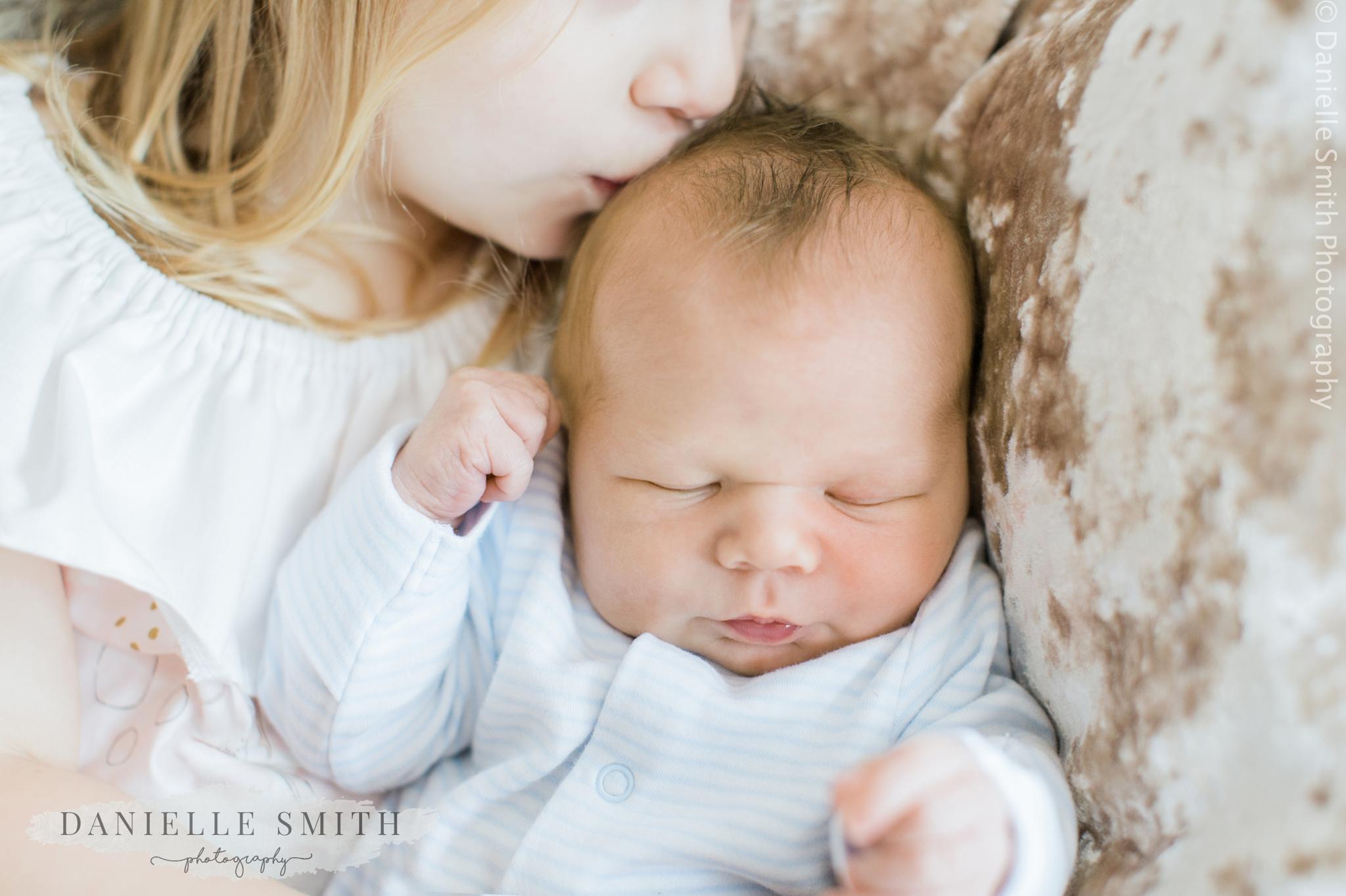big sister kissing baby brothers head