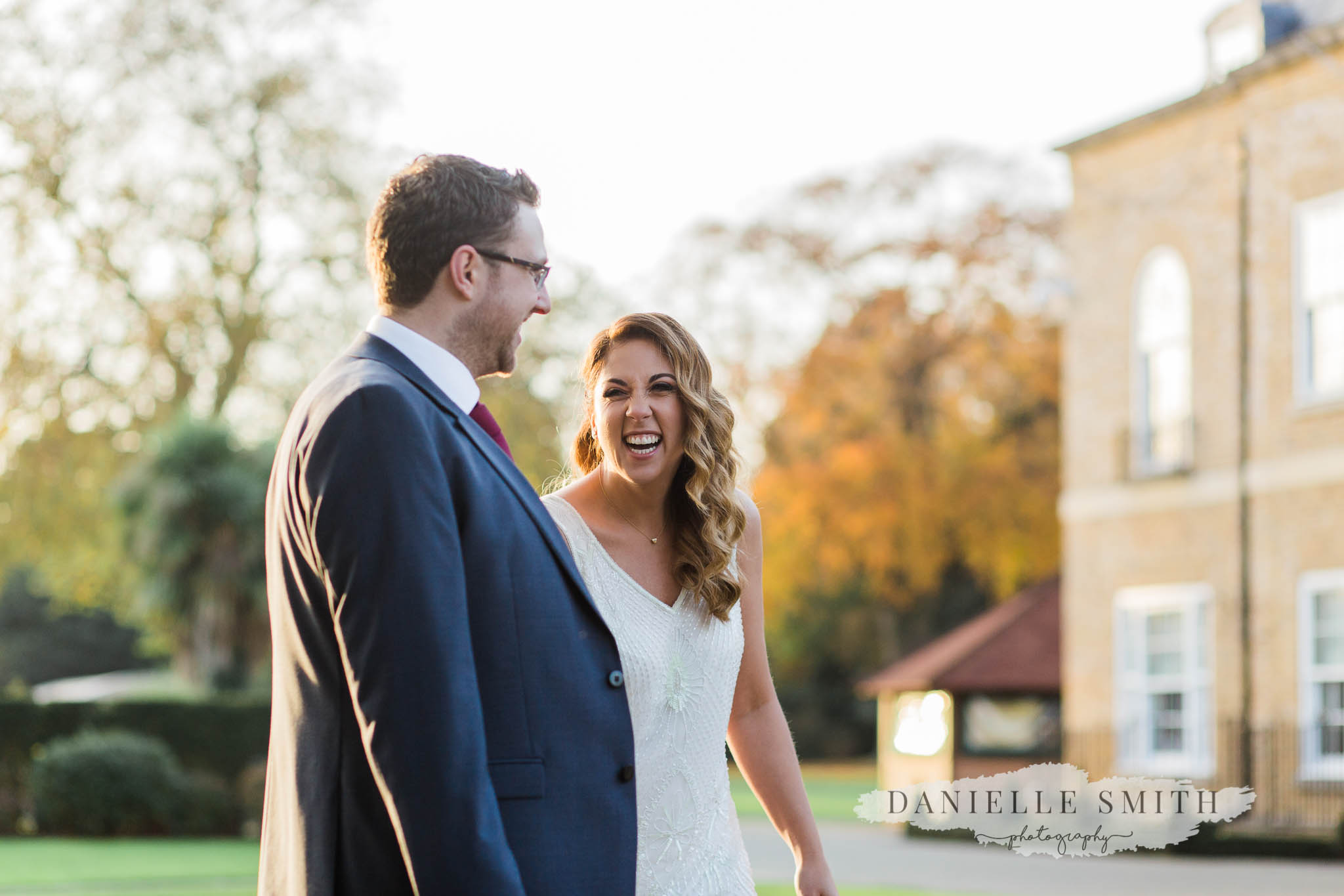 bride and groom walking and laughing - orsett hall wedding photographer