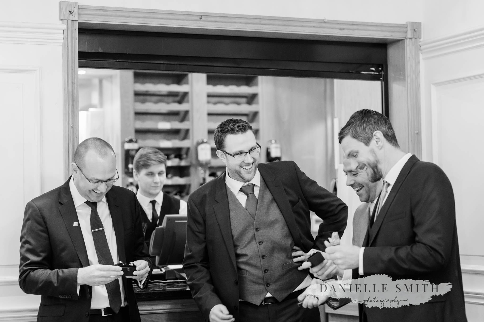 groom and groomsmen laughing at wedding gifts