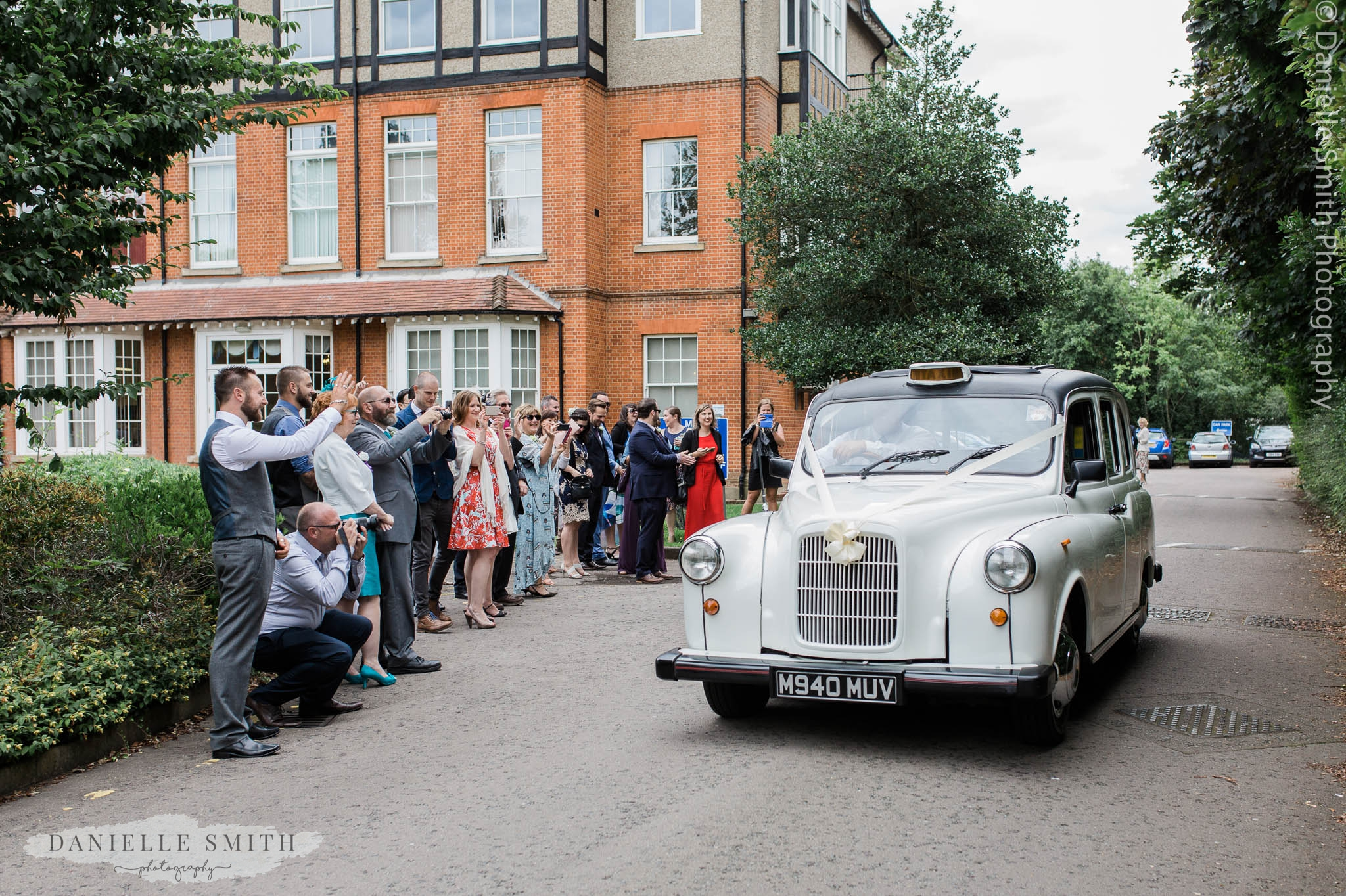 wedding guests waving off bride and groom in white taxi